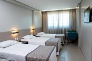 A bed or beds in a room at Hotel Porto Jatiuca