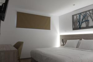 A bed or beds in a room at Vallian Village Hotel