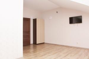 A television and/or entertainment center at Hotel Chernomorsky Complex of Townhouse