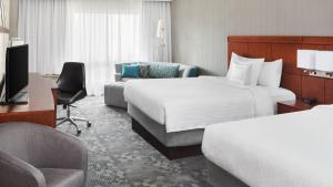 A bed or beds in a room at Courtyard By Marriott Jersey City Newport