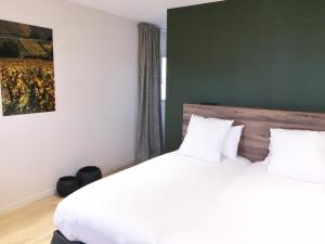 A bed or beds in a room at Aux Terrasses