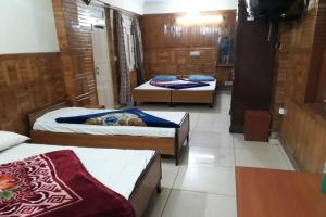 A bed or beds in a room at Goroomgo Kohinoor Nanital