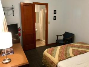 A bed or beds in a room at Chalet Motel
