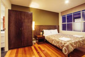 A bed or beds in a room at YTI Garden Hotel