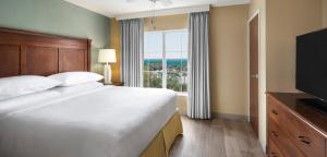 A bed or beds in a room at Embassy Suites Destin Miramar Beach