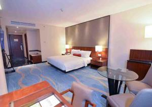 A bed or beds in a room at Gumaya Tower Hotel