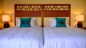 A bed or beds in a room at The Uza Terrace Beach Club Villas