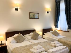 A bed or beds in a room at Hotel Patria Zakopane