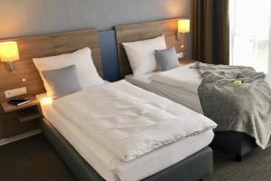 A bed or beds in a room at StadtHotel ARTE