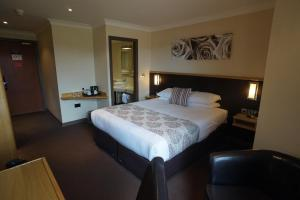 A bed or beds in a room at Damon's Hotel