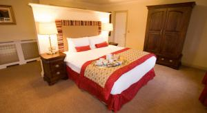 A bed or beds in a room at Bracken Court Hotel