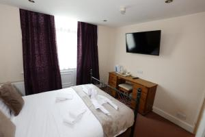 A bed or beds in a room at Aylesbray Lodge
