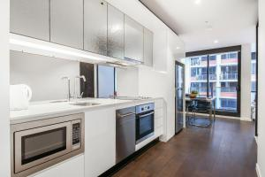 A kitchen or kitchenette at A Cozy CBD Suite Near Southern Cross + Pool & Gym