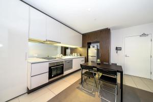 A kitchen or kitchenette at A Cozy Suite with a View of Docklands & The Yarra