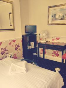 A bed or beds in a room at The Royal Standard Guest House