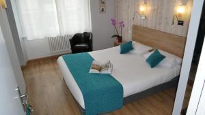 A bed or beds in a room at Hôtel des Halles - Concarneau