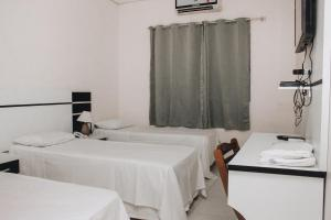 A bed or beds in a room at Samir Hotel Business