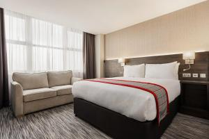 A bed or beds in a room at Ramada East Kilbride