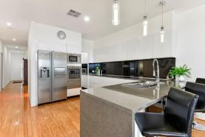 A kitchen or kitchenette at BENGALEE EXECUTIVE TOWNHOUSE- MODERN & STYLISH