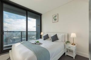 A bed or beds in a room at Face to ANZ Stadium Two Bedder Apt