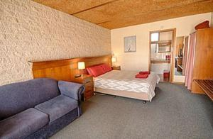 A bed or beds in a room at Darlot Motor Inn