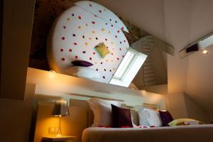 A bed or beds in a room at Hotel Design Secret de Paris