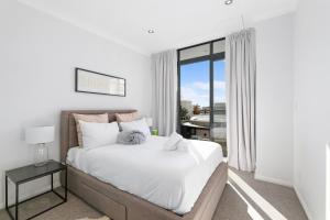 A bed or beds in a room at Darling Harbour Penthouse Views+Jacuzzi
