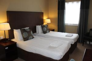 A bed or beds in a room at Cairn Hotel