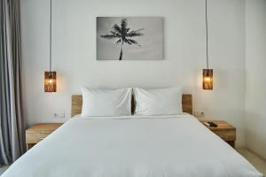 A bed or beds in a room at Sikara Lombok Hotel