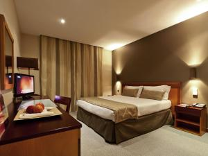 A bed or beds in a room at Hotel Mercure Figueira Da Foz