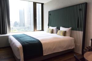 A bed or beds in a room at THE KNOT TOKYO Shinjuku