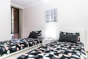 A bed or beds in a room at CP233-Cosy 2 bedroom Apt in Pyrmont 5 mins to ICC