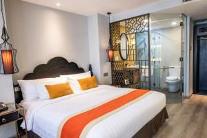 A bed or beds in a room at Sanouva Saigon Hotel