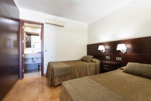 Een bed of bedden in een kamer bij TC Apartamentos Rocamar