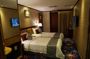 A bed or beds in a room at Macau Masters Hotel