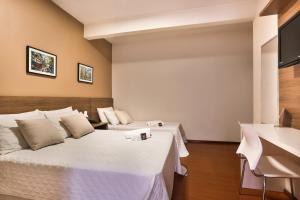 A bed or beds in a room at Zallon Hotel Executivo