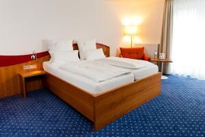 A bed or beds in a room at Komforthotel Butjadinger Tor