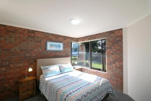 A bed or beds in a room at Pelican Waters