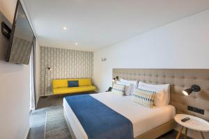 A bed or beds in a room at Allegro Madeira - Adults Only