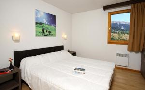 A bed or beds in a room at Résidence Le Chalet de L'Eterlou by Popinns