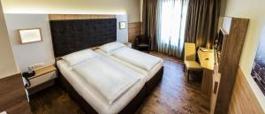 A bed or beds in a room at Goldenes Theater Hotel Salzburg