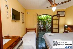 A bed or beds in a room at VELINN Pousada dos Marinheiros