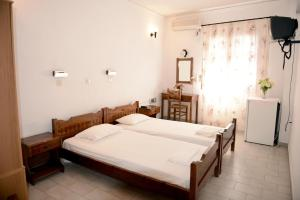 A bed or beds in a room at Anthemis Hotel