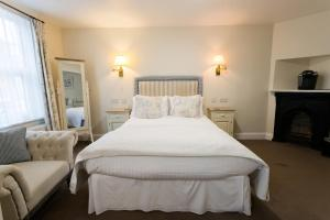 A bed or beds in a room at The Old Fourpenny Hotel