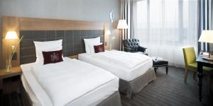 A bed or beds in a room at Mövenpick Hotel Stuttgart Airport