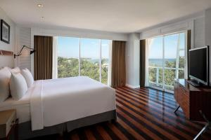A bed or beds in a room at The Kuta Beach Heritage Hotel - Managed by Accor