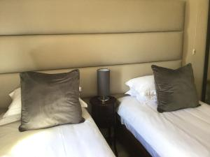 A bed or beds in a room at The Capital Guest House