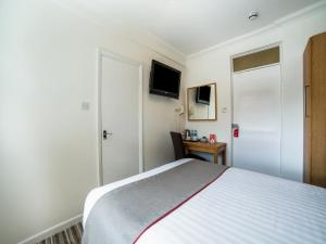 A bed or beds in a room at OYO Kingsley Hotel