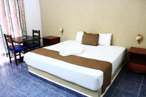A bed or beds in a room at Hotel Maya del Carmen