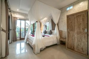 A bed or beds in a room at Adi Bisma Inn